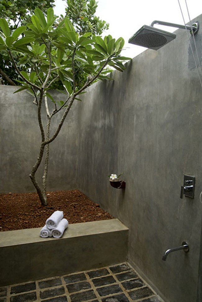 Outdoor bathroom with large rain shower and cemented wall