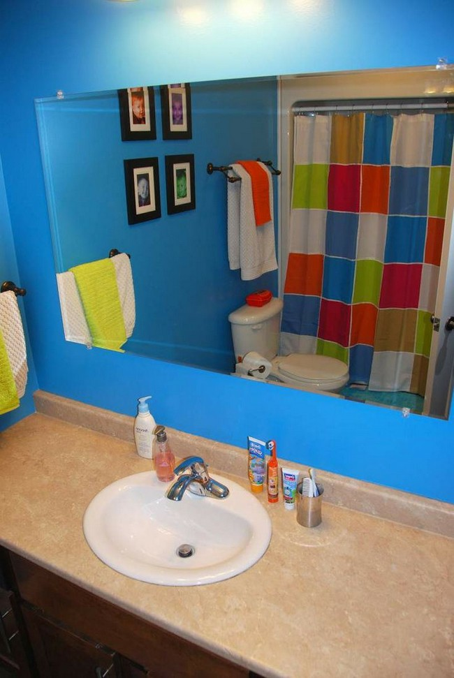 Bathroom with bright blue wall and colorful shower curtain
