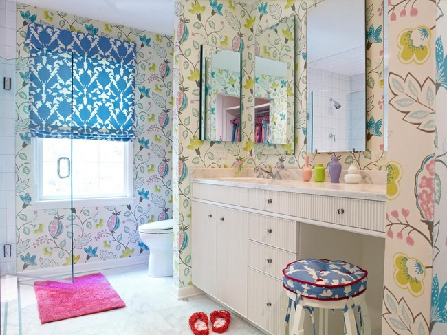 Bathroom with mirrors and colorful prints in wallpaper and shower curtain