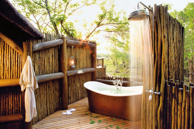 Outdoor bathtub and rain shower enclosed in a bamboo structure