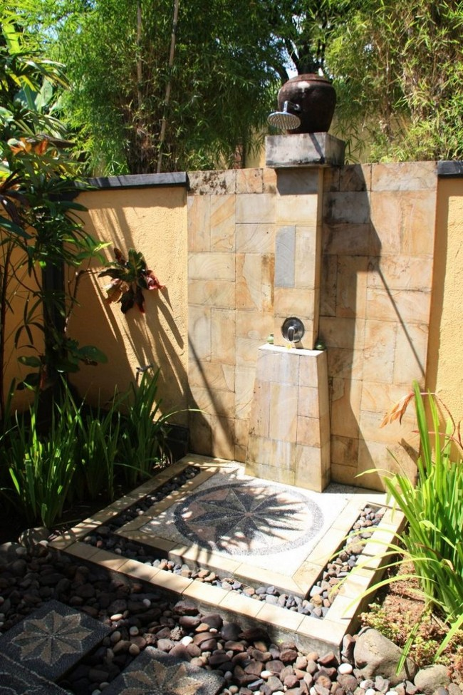 Stand-alone outdoor shower with plenty of small rocks