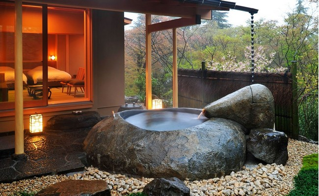 Outdoor tub carved out of a rock, surrounded by pebbles and stone terrace
