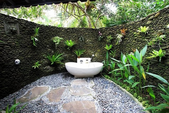 Stone outdoor bathroom with plenty of flowers