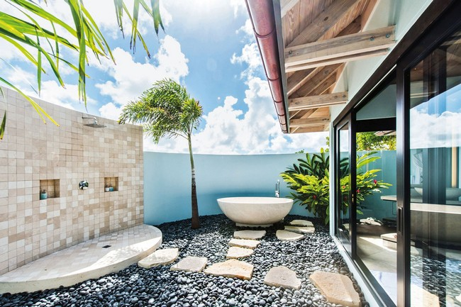 Tropical-style bathroom with tiles, stone and blue wall