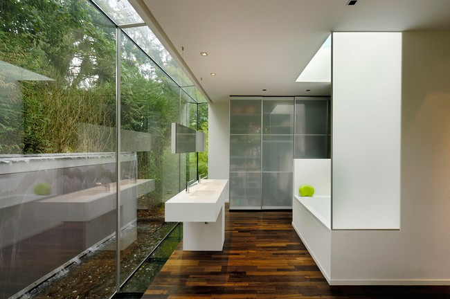 Outdoor bathroom with white color scheme and extensive glass wall that lets in sunlight