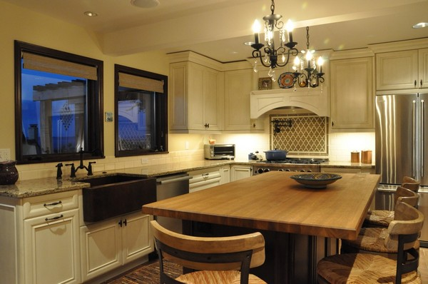Simple wrought iron chandeliers that match the wrought iron finishes of the furniture throughout the kitchen