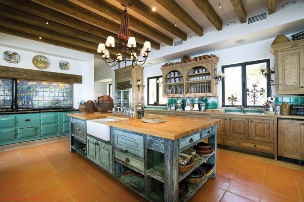 Bluish-green cabinets and tile backsplash that adds color and exuberance to the otherwise dull Spanish style kitchen