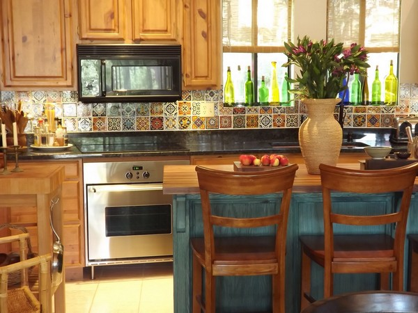 Bright flowers and windows that let in plenty of light make this small Spanish style kitchen appear livelier.