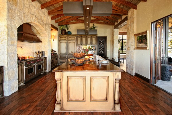 Spanish-style kitchen with high ceiling with wooden and metal beams