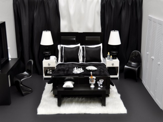Small bedroom with heavy black drapes and white rug