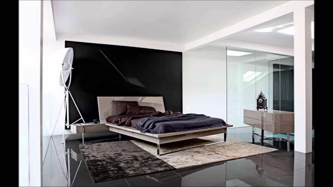 Black and white bedroom with a shiny, black stone floor and neutral décor pieces