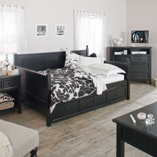 Pale hardwood flooring adds simple neutral elegance to this black and white bedroom