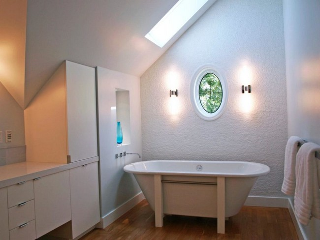 Recessed lighting in this bathroom has the outcome of nullifying the effect of the slanted ceiling, by making the bathroom appear larger