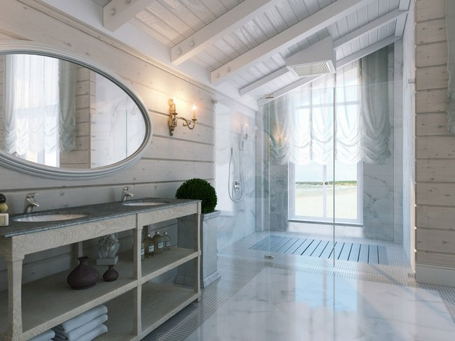 Large oval mirror which reflects light making bathroom appear more airy