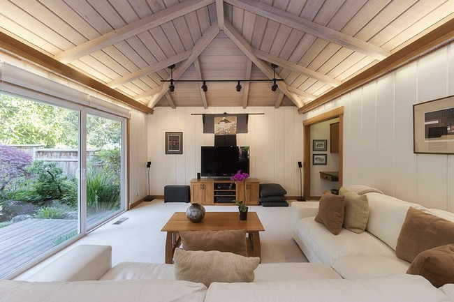Slightly slanted hardwood ceiling with beams, inducing a rustic charm
