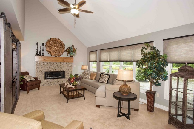 Stone fireplace adds warmth to living room with slanted ceiling