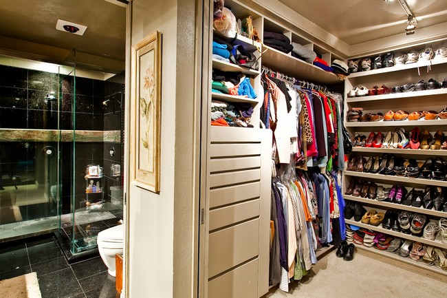 Elegant walk-in-closet with a large glass door and floor-to-ceiling shoe rack