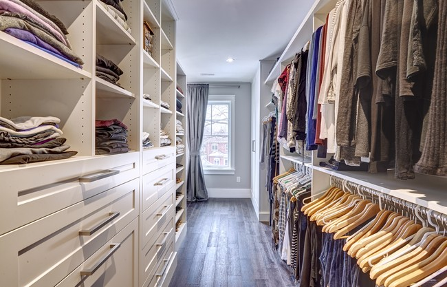 Large walk-in-closet with blue and white color scheme, creating a bold and masculine appearance