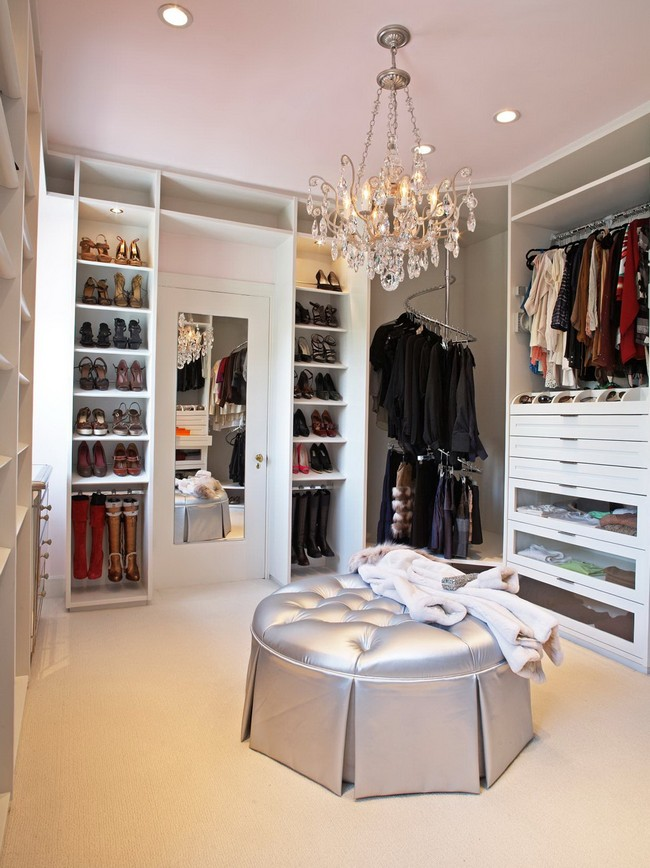 Extravagant contemporary women's closet with a crystal chandelier hanging over a silvery pouffe