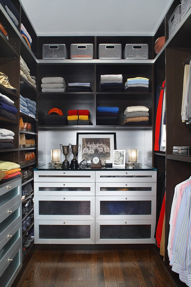 Men's closet with drawers that have frosted doors, paired with a dark hardwood floor