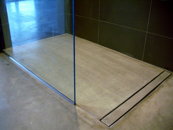 Small walk-in shower with tile wall and glass closure