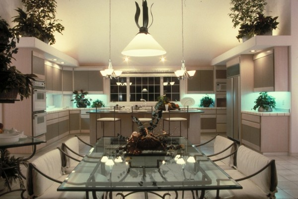 Large kitchen with dining area fitted with a metal dining table that has a glass countertop